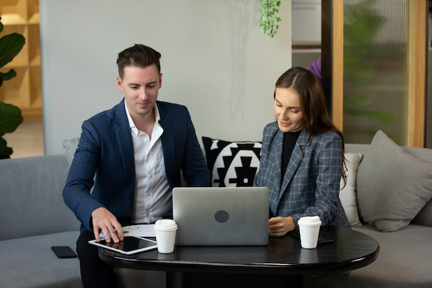 디지털 태블릿 및 컴퓨터를 사용하여 사무실에서 말하는 사업 사람들