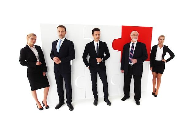 비즈니스 사람들이 팀과 흰색 배경에 고립 된 조립 된 퍼즐