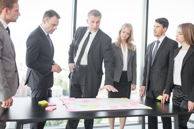 스틱 메모를 사용하여 사무실 책상에 계획을 개발하는 비즈니스 사람들 팀