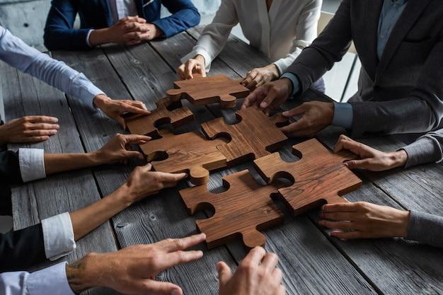 ミーティングテーブルの周りに座って、木製のジグソーパズルのピースを組み立てるビジネスマンチーム団結協力アイデアコンセプト
