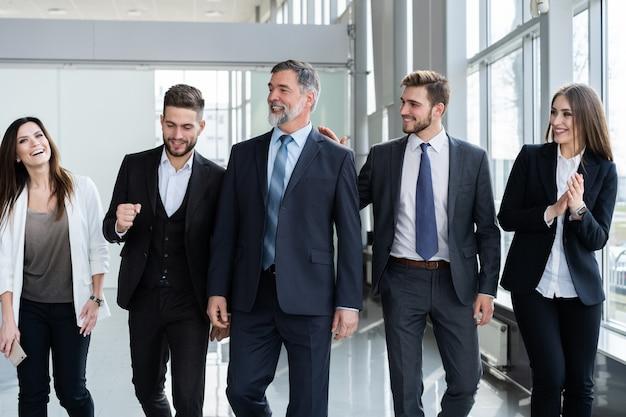 Группа деловых людей, идущая в современном офисе со зрелым лидером на переднем плане