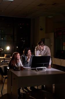 Команда деловых людей работает поздно ночью с помощью компьютера. концепция сверхурочных часов. время мозгового штурма, пропустите крайний срок. вид сбоку на кавказской бизнес-команде, работающей над обсуждением проекта