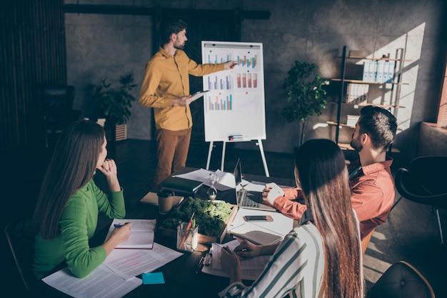 Тренер деловых людей показывает на графики, показывающие рост корпоративного дохода, проводит семинар для студентов, планирующих стать предпринимателями в будущем