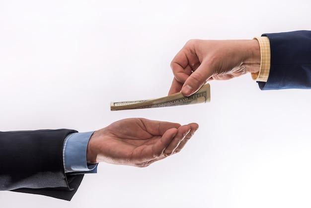 ビジネスマンは私たちに灰色の背景に分離されたお金を転送します