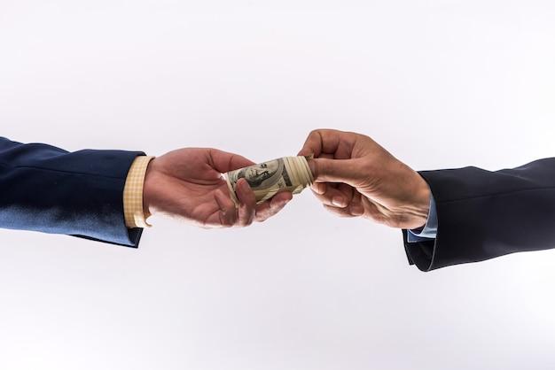 ビジネスマンは灰色の壁に隔離されたお金を私たちに送金します。金融の概念