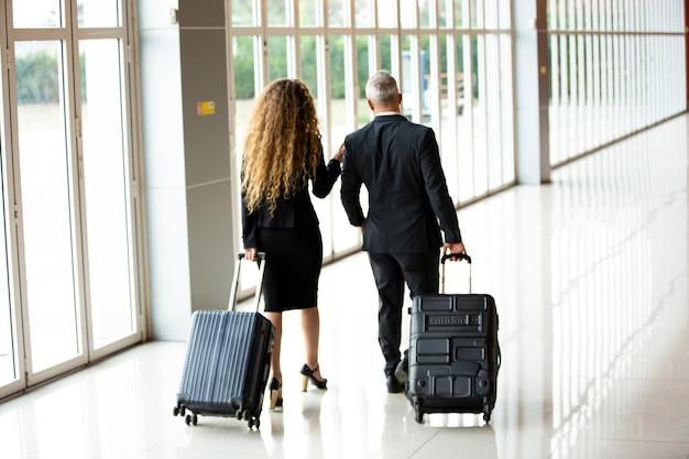 ビジネスマンは空港ターミナルで旅行します