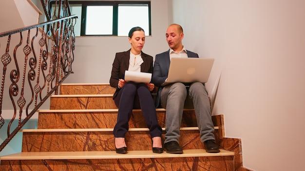 金融会社の階段に座っているレポートを分析するクリップボードからドキュメントを読んでラップトップで入力するビジネスマン。金融の職場を歩いているプロのビジネスマンのグループ。