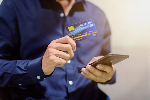 비즈니스 사람들은 스마트 폰을 통해 신용 카드를 사용하여 거래하고 쇼핑하고 비즈니스를 수행합니다.