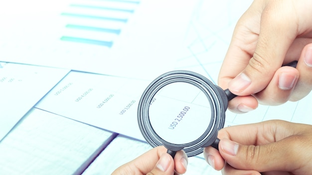 Business people use a magnifying glass to analyze the company's data and statistics
