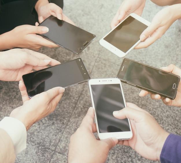 사업 사람들은 네트워크 이메일 채팅 온라인 응용 프로그램을 통해 서로 통신하는 휴대 전화를 사용합니다.