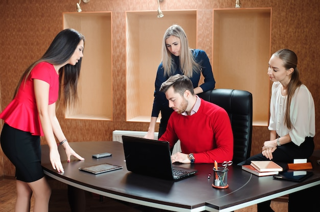 Business people using laptop at conference table.