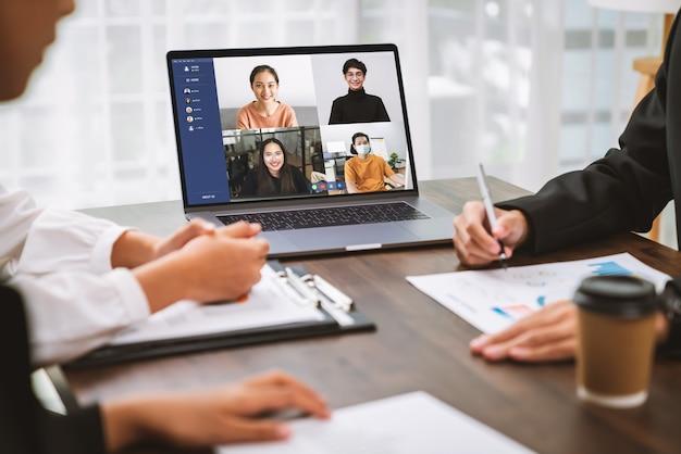 テーブルの上でラップトップを使用し、ビデオ通話会議を行ってオンラインでチームを組み、作業プロジェクトを提示するビジネスマン。在宅勤務のコンセプト。