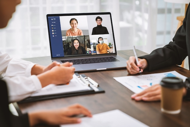 Business people using laptop on table with making video call meeting to team online and present work projects. concept working from home.