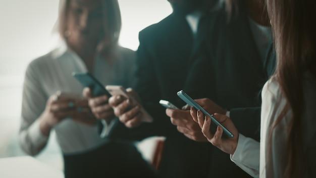 Деловые люди, используя мобильные телефоны вместе, стоя в офисе. закройте выстрел из человеческих рук, держа смартфоны. размытое изображение. селективный фокус на женской руке на переднем плане.