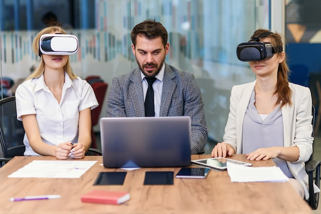 Business people using virtual reality goggles during meeting. team of developers testing virtual reality headset and discussing new ideas to improve the visual experience.