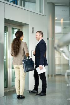 Деловые люди ждут на лифте