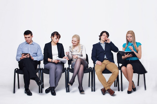 Business people waiting in queue sitting in row holding smartphones and cvs, human resources, employment and hiring concept