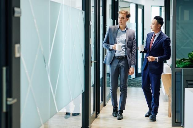 Business people walking along office corridor