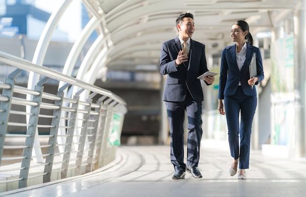現代のオフィスの前を歩いて話し合うビジネスマン