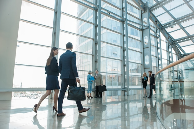 Деловые люди, идущие в современном стеклянном офисном здании
