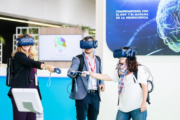 Business people wear virtual reality glasses at a congress