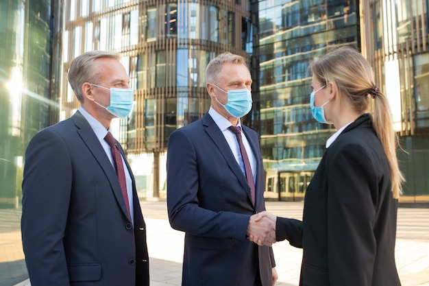 Business people wearing face masks, standing near office buildings, shaking hands, meeting and talking in city. side view, low angle. business during outbreak concept