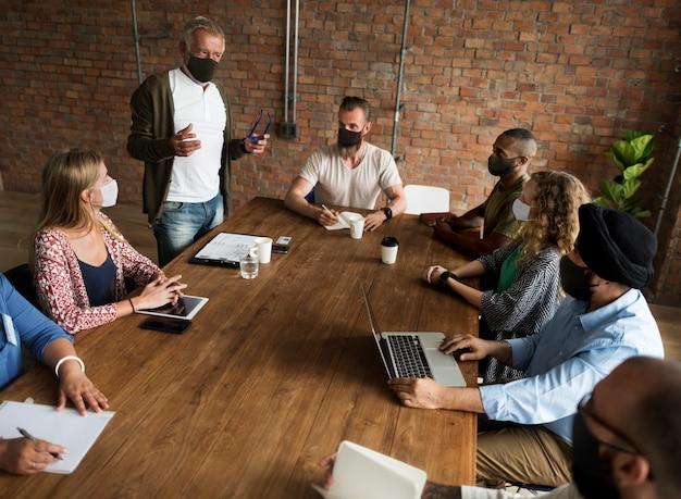 Uomini d'affari che indossano maschere durante la riunione sul coronavirus