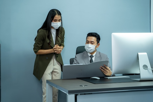 Business people wearing protective face mask while working together during coronavirus epidemic.