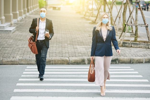 通りを歩いたり、道路を横断するときに保護マスクを着用しているビジネスマン