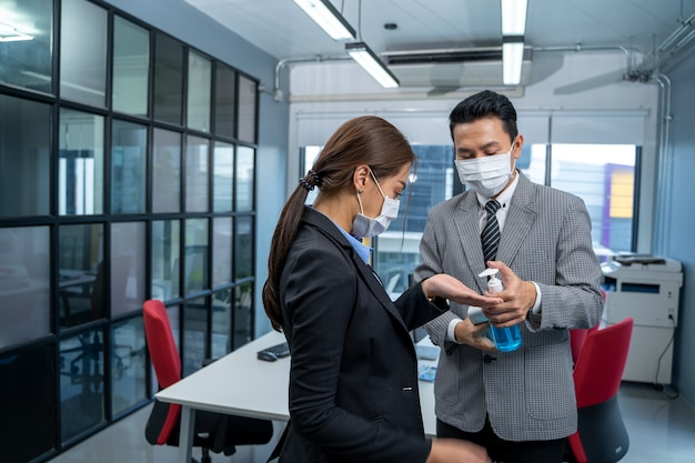 Business people with face mask protect are disinfecting hands at office after covid-19 quarantine.