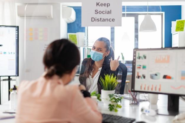 코로나바이러스 세계적 대유행 동안 재정 프로젝트에 대해 논의하는 새로운 일반 회사 사무실에서 일하는 얼굴 마스크를 쓴 사업가들. 동료들은 바이러스 질병을 피하기 위해 사회적 거리를 유지합니다.