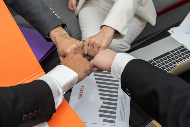 Business people with fist bump together in teamwork at the office above desk with document.