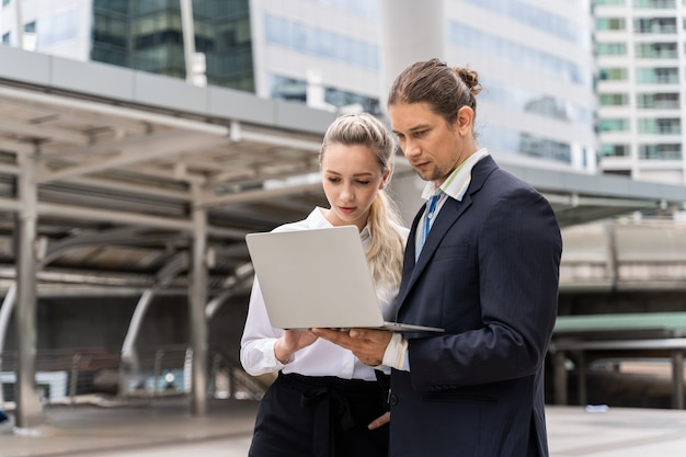 ラップトップコンピューターの議論と屋外で一緒に働くビジネスマン