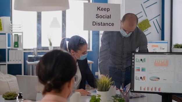 Деловые люди в медицинских масках сидят в новом нормальном офисе компании и анализируют финансовый проект во время пандемии covid19. коллеги сохраняют социальное дистанцирование, чтобы избежать вирусных заболеваний