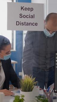 Covid19 전염병 동안 재정 프로젝트를 분석하는 새로운 일반 회사 사무실에 앉아 의료용 안면 마스크를 쓴 사업가들. 바이러스 질병을 피하기 위해 사회적 거리를 유지하는 동료