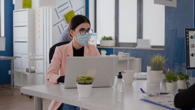 Business people with medical face masks working together in new normal office during coronavirus pandemic. company team respecting social distancing to avoid infection with covid19