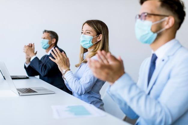 近代的なオフィスで成功したビジネス会議の後、保護マスクのビジネスマンが手をたたく
