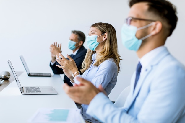 Business people with protection masks clapping hands after successful business meeting in the modern office