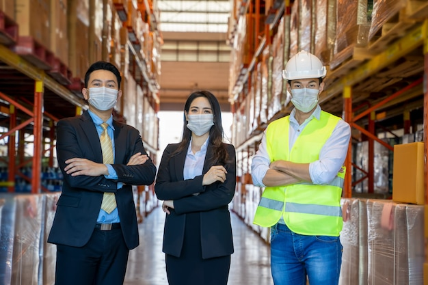 Business people with warehouse workers wearing hard hats standing in aisle between tall racks with packaged goods, warehouse workers in warehouse with managers.