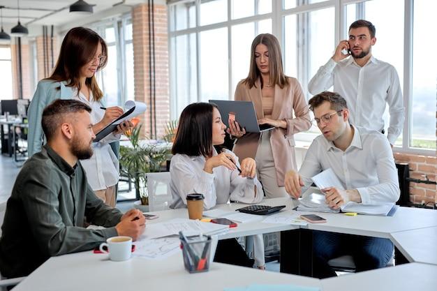 現代のオフィスでチームとして働き、事業計画や戦略について話し合うビジネスマンは、アイデアを共有します。テーブルの後ろに座っている間、会話、コミュニケーションを持っているフォーマルな服装の白人男性と女性