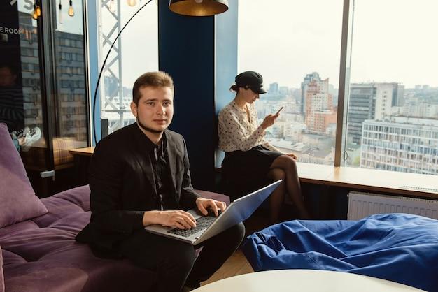パノラマの窓と現代のオフィスで働くビジネスマン