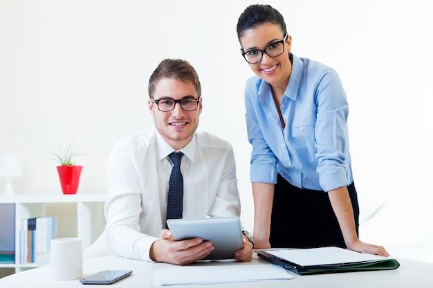 Деловые люди, работающие в офисе с цифровым планшетом.
