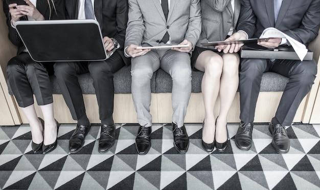 로비에서 행에 앉아 무릎에 노트북과 문서를 들고 함께 일하는 사업 사람들