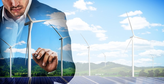 Business people working over wind turbine farm and green renewable energy worker interface.