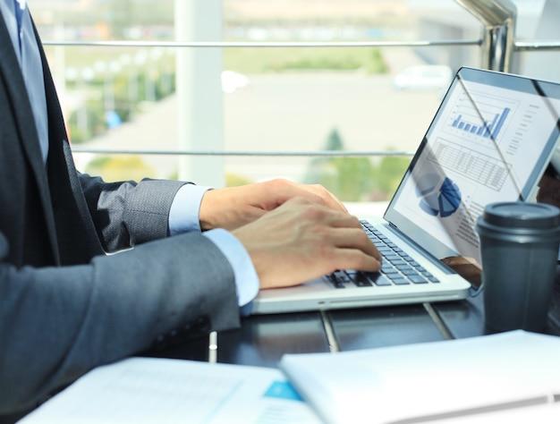 ノートパソコンの画面に表示される財務統計を分析するビジネスパーソン。