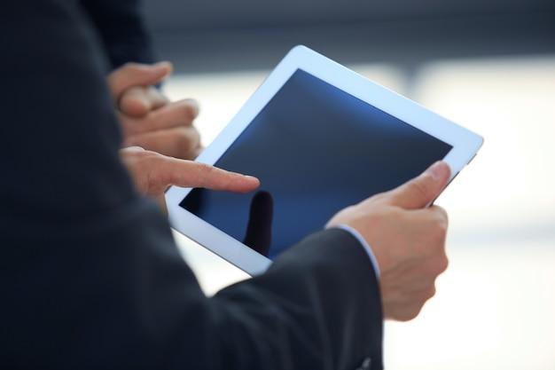태블릿 화면에 표시된 재무 통계를 분석하는 비즈니스 사람