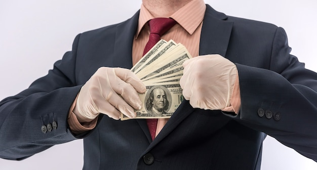 Business person hand in blue protective gloves with money isolated on white background. save protect concept covid 19 coronavirus