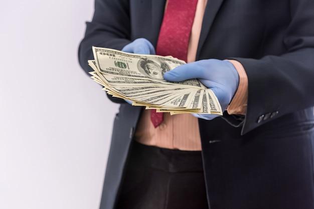 ビジネスパーソンお金が分離された青い保護手袋を手に