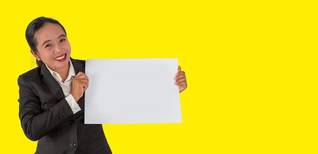 Business person holding a blank white paper in hand isolated on yellow background.