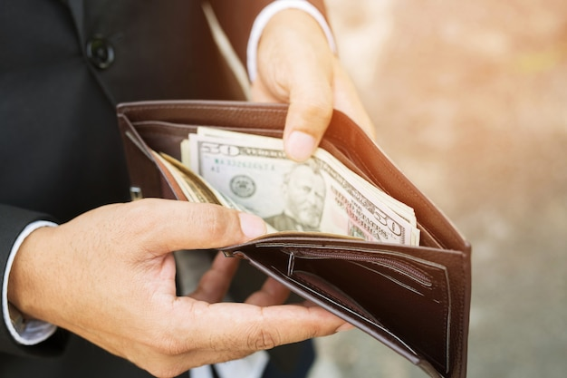 Business person holding an wallet in the hands of an man no money have a little money. poverty poor bankruptcy  in concept.